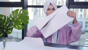 Small business and hobby concept. Muslim woman fashion designer pinning paper pattern at the table in tailor shop.  stock video