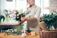 Smiling lovely young woman florist arranging plants in flower shop Royalty Free Stock Photos