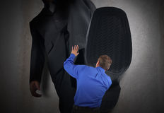 Small Business Man Fear Stepped On. A little business man is under a big bosses foot about to crush or step on him. His hands are in the air scared Stock Images