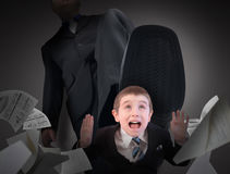 Small Business Man Fear Stepped On. A little business man is under a big bosses foot about to crush or step on him. His hands are in the air scared Stock Image