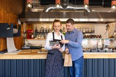 Small business owner couple in little family restaurant looking at tablet for online orders stock image