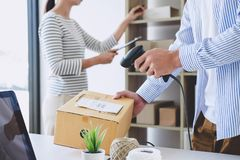 Small business owner delivery service and working packing box, business owner working checking order to confirm before sending. Customer in post office royalty free stock image