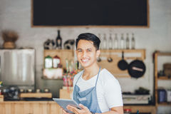 Small business owner at his coffee shop. Portrait of small business owner at his coffee shop using tablet pc stock photos