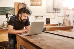 Small business owner in his workshop studio with laptop royalty free stock photography