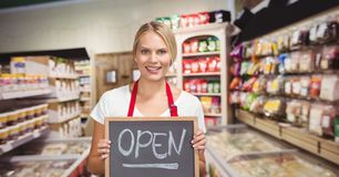 Small business owner holding a small blackboard with the word open. Digital composite of Small business owner holding a small blackboard with the word open Stock Photos