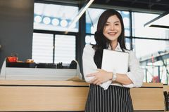 Small business owner holding tablet at counter in coffee shop. f. Small business owner holding tablet at counter in coffee shop. asian female barista wearing Royalty Free Stock Image