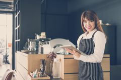 Small business owner holding tablet at counter in coffee shop. f. Small business owner holding tablet at counter in coffee shop. asian female barista wearing royalty free stock images