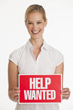 Small business owner holding up Help Wanted sign Stock Image
