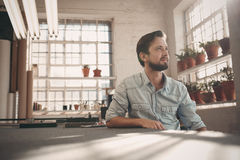 Small business owner looking away thoughfully in his studio. Handsome young male small business owner sitting in his studio workshop thinking positively while royalty free stock photos