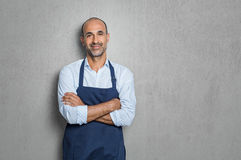 Small business owner. Mature man wearing blue apron isolated on grey background with copy space. Successful senior man wearing apron with crossed arms on grey stock photo