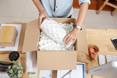 Woman packing vase. Small business owner packing vase to send it to customer, view from above royalty free stock image