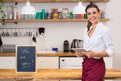Small business owner. Portrait of young happy waitress looking at camera at bar with digital tablet. Portrait of a young female chef holding digital tablet with Royalty Free Stock Photos