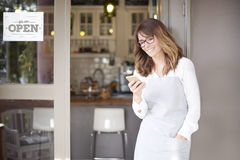 Small business owner. Shot of a happy confident cafe owner standing at doorway and text messaging. Small business royalty free stock image