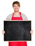 Small business owner sign. Small business owner showing blank empty blackboard sign wearing apron. Handsome young shop owner man isolated on white background stock photos