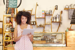 Small business owner using a tablet in her coffee shop. Beautiful cafe owner running her small business with the help of a digital tablet while standing near the royalty free stock images