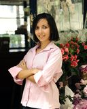 Small business owner: woman and her flower shop. Small business owner: proud woman and her flower shop royalty free stock photography
