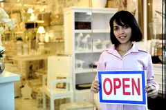 Small business owner: woman holding an open sign