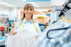 Small business owner woman in a textile cleaning shop. Smiling small business owner woman in a textile cleaning shop royalty free stock images