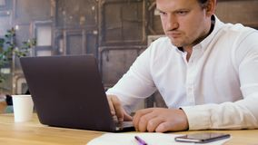 Small business owner working on laptop. Businessman working on a laptop in small business office for startup team stock footage