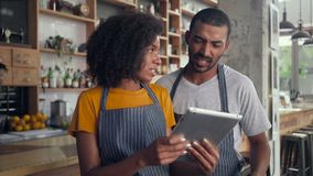 Happy business partners using digital tablet in cafe stock footage