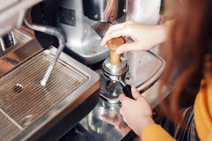 Small business, people and service concept - woman or waiter in apron with holder and tamper preparing coffee at coffee. Shop Stock Photo