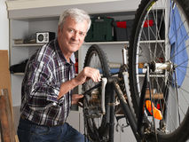 Small business. Portraif of retired man standing next to bike and working at his workshop. Small business Royalty Free Stock Image