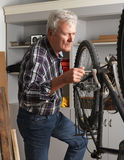 Small business. Portraif of retired man standing next to bike and working at his workshop. Small business Stock Image