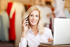 Small business. Portrait of small fashion store owner. Busy businesswoman sitting in her designer shop and making call while and using laptop Royalty Free Stock Image