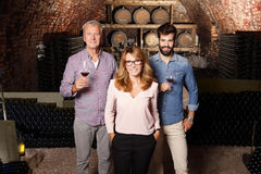Small business. Portrait of multigenerational winery owner family standing at wine cellar. Senior winemaker and young sommelier standing at background and Stock Photo