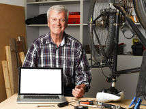 Small business. Portrait of senior bike shop owner sitting at desk behind the laptop with white screen. Active old man looking at camera and smiling. Small Royalty Free Stock Photo