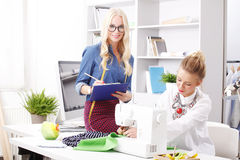 Small business. Portrait of young businesswomen working together in designer studio. Fashion designer holding in her hand a clipboard and making notes while Royalty Free Stock Photo