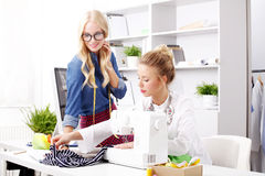 Small business. Portrait of young businesswomen working together on new project while sitting at designer studio in front of sewing machine and computer. Smiling Royalty Free Stock Photography