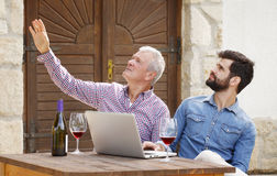 Small business. Portrait of young and senior men tasting with red wine at wine cellar. Professional winemakers sitting at desk in front of laptop and consulting Royalty Free Stock Photos