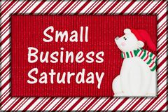 Small Business Saturday message. Red shiny fabric with a candy cane border and a Santa polar bear with text Small Business Saturday stock photos