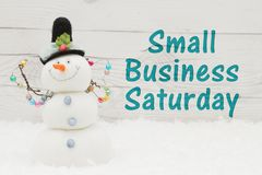 Small Business Saturday message. Some snow and a snowman on weathered wood with text Small Business Saturday royalty free stock photography