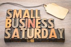 Small Business Saturday in wood type. Small Business Saturday word abstract - text in vintage letterpress wood type with a blank price tag, holiday shopping Royalty Free Stock Images