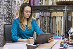 Small business, shop, show room of fabrics and accessories for the interior. Woman looks at a digital tablet, selects fabrics, dra stock images