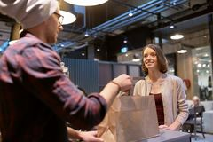 Seller giving paper bag and money to woman at cafe. Small business, takeaway food, people and service concept - men or seller giving paper bag and money change Royalty Free Stock Photography