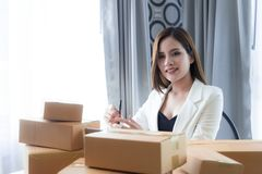 Business woman is preparing to send out her product in boxes. Small business woman is preparing to send out her product in boxes Royalty Free Stock Photos
