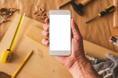 Small business woodwork entrepreneur holding smartphone with mock up screen. Small business woodwork entrepreneur holding modern smartphone device with blank stock images