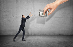 Small businessman on concrete background reaching out for a giant hand holding money. Stock Photos