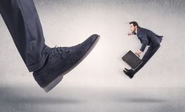Small businessman kicked by big shoe Stock Photography