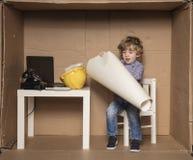 Small businessman develops building plans, cardboard office. Small business man develops building plans, cardboard office Stock Photography