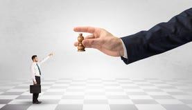 Businessman fighting against big chessman on a big hand. Small businessman fighting against big chessman on a big hand with chess board concept Stock Photos