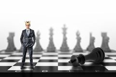 A small businessman with a golden crown on his head stands on a chessboard near a fallen black king. stock image