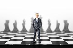 A small businessman with a golden crown on his head stands on a giant chessboard. royalty free stock images