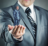 Small businessman in hand. Hand giving small confident businessman royalty free stock image