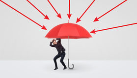 A small businessman hiding under a large red umbrella that protects him from red arrows. Business and competition. Safety and protection. Insurance from loss Stock Images