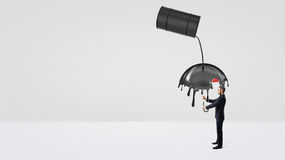 A small businessman hiding under an umbrella from crude oil leaking of a large black barrel. Royalty Free Stock Image