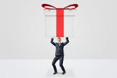 A small businessman holding a giant gift box with both hands above his head. Stock Photo